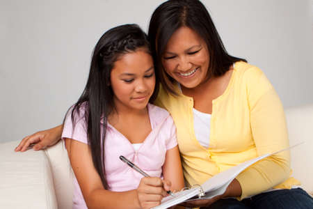 Mother helping her daughter with homework.