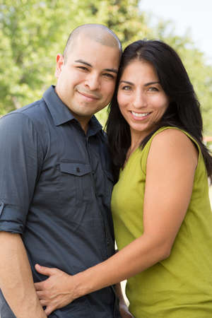 Portrait of a young Hispanic couple smiling.