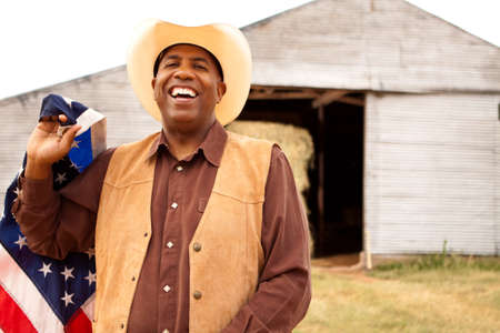 African American cowboy holding an American flag.