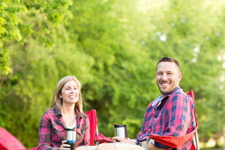 Couple talking and laughing on a camping trip. Stock Photo