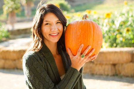 Young woman holding a pumpkin in a fall setting.