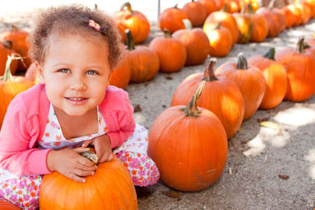 Little girl smiling at a pumpking patch. Stock Photo
