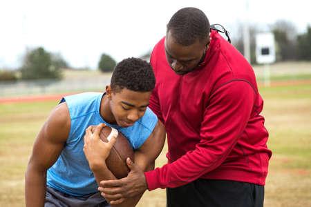 Coach training a high school athlete.