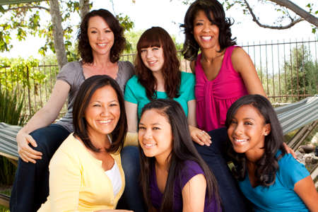 Diverse group of mothers and daughters laughing and smiling.