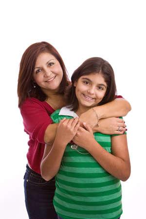 Hispanische Mutter umarmt ihre Tochter isoliert auf weißem..