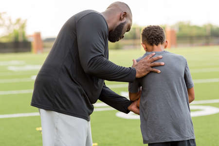 American Football coach training a young athlete. Stockfoto