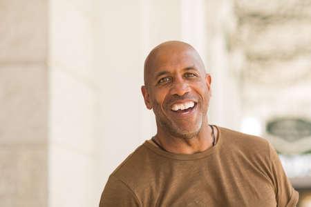 Mature African American man smiling wearing glasses.