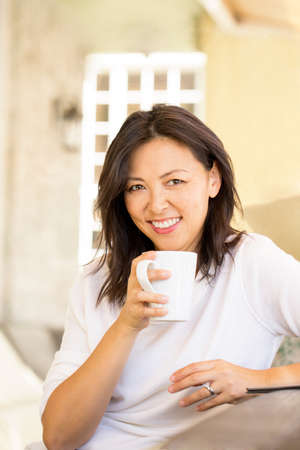 Portrait of an Asian woman smiling and drinking coffee.