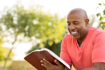 African American man praying and reading the Bible. Banco de Imagens