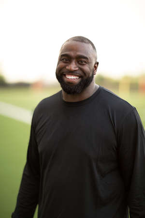 Portrait of an African American Football coach smiling.