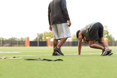 American Football coach training a young athlete. Stock Photo