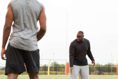 American Football coach training a young athlete. 免版税图像