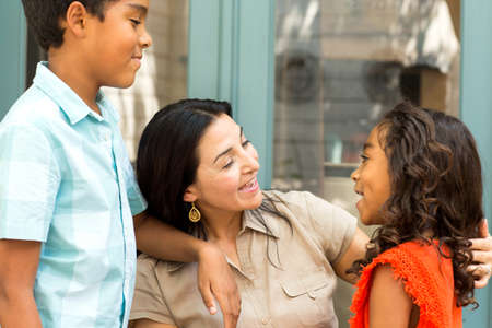 Gelukkige Spaanse moeder die lacht en praat met haar kinderen.