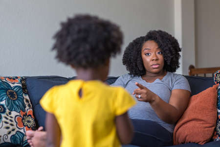 African American mother disciplining parenting her young child. Imagens