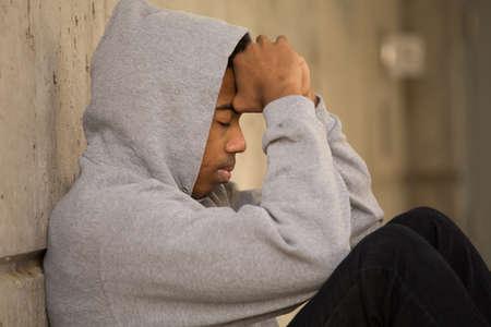 African American young teenage boy feeling depressed.