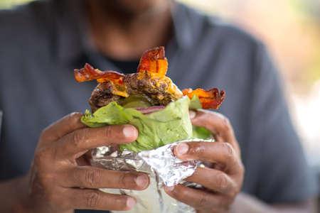 African American man eating a burger without a bun. Stok Fotoğraf
