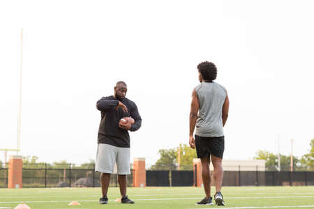 American Football coach training a young athlete. Stock fotó