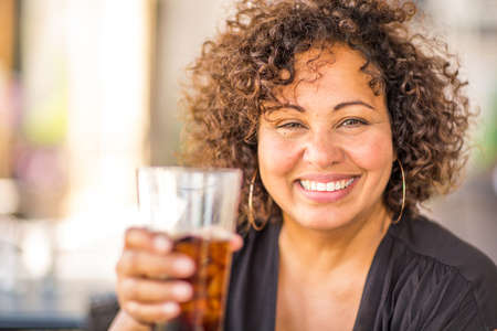 Portrait of a woman at a restaurant having a drink.