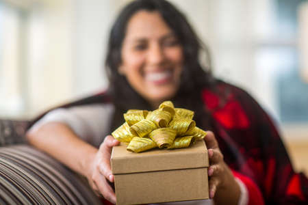 Happy woman wrapped in a cozy blanket holding a gift.