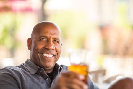 Mature African American man drinking at a restaurant.