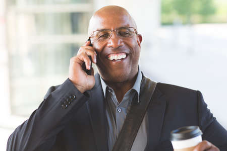 African American businessman drinking coffee and texting. 写真素材