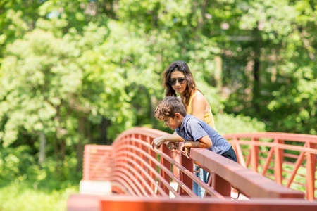 Portrait of a woman standing on a bridge with her children. 写真素材
