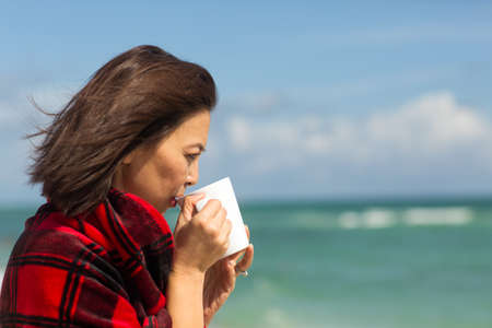 Portrait of a happy Asian woman drinking coffee.