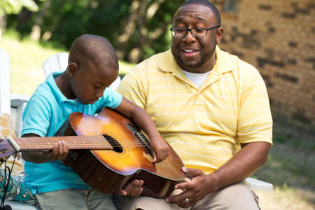 Father teaaching his his son to play the guitar.