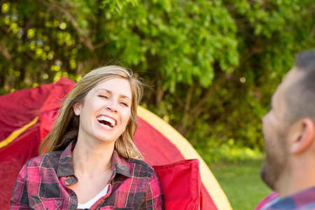 Couple talking and laughing on a camping trip. 写真素材