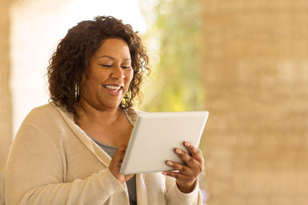 Smiling African American woman working on a tablet. 写真素材