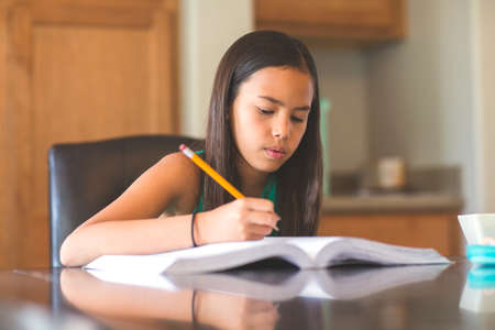Young Girl Sitting At A Desk And Working On Her Homework 版權商用圖片