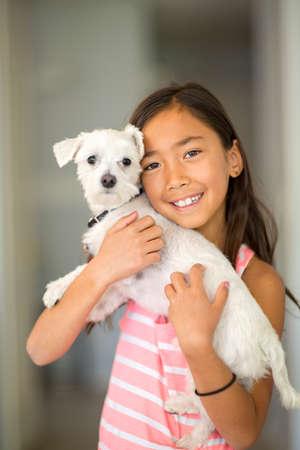 Little girl giving her dog a big hug.