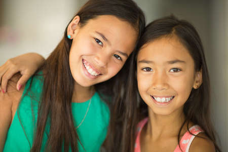 Portrait of cute little girls hugging and smiling. 写真素材