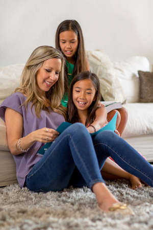 Mother Reading To Her Daughters And Helping Them With Their Homework 写真素材