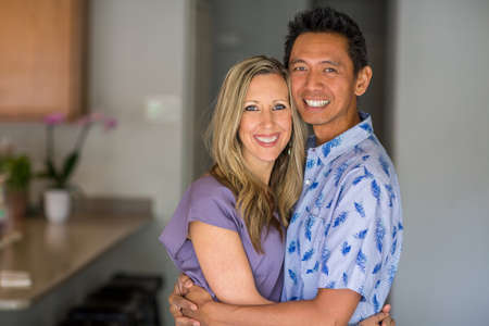 Portrait of a mixed race couple smiling and hugging.