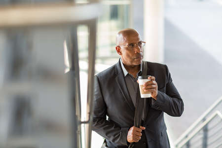 African American businessman walking and drinking coffee.