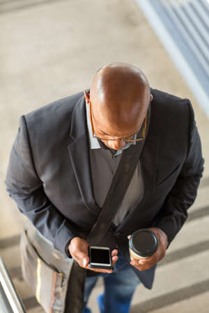 African American businessman drinking coffee and texting. Stock Photo