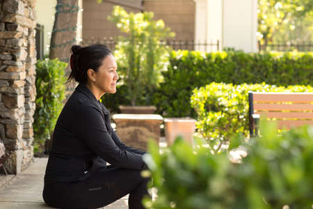 Portrait of a fit Asian woman sitting outside thinking.