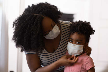 African American mother helping her daughter put on a face mask. Stock Photo