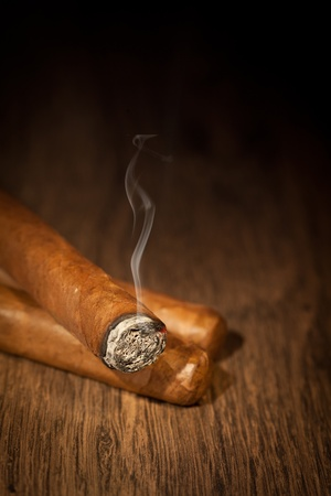 Typical havana cigars on wooden background Фото со стока