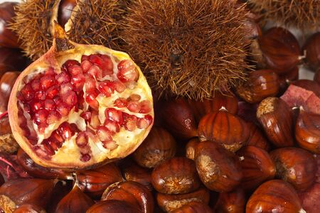Autumn composition with chestnuts and red pomegranate photo