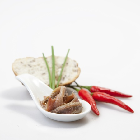 Delicious salted anchovies with oil on white background