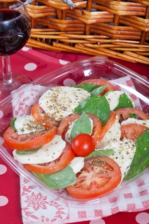 Fresh italian caprese salad with mozzarella, tomatoes and basil photo