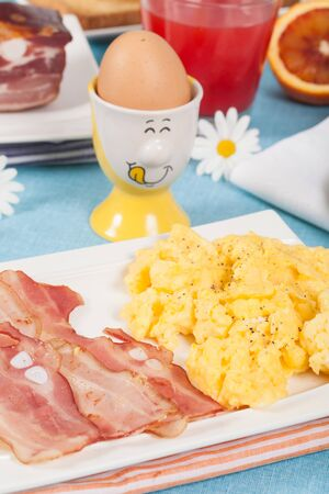 Breakfast with scrambled eggs and crispy bacon photo