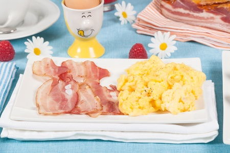 scrambled eggs: El desayuno con huevos revueltos y bacon crujiente
