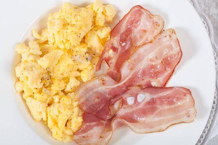 scrambled eggs: Desayuno con huevos revueltos y bacon crujiente
