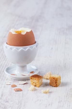 Boiled egg served on elegant white cup Imagens