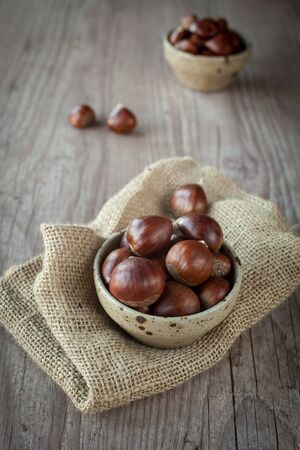 Bunch of fresh chestnuts in a bowl on wooden table photo