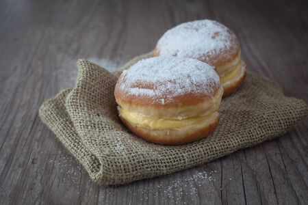 Delicious krapfen with cream on a wooden background photo