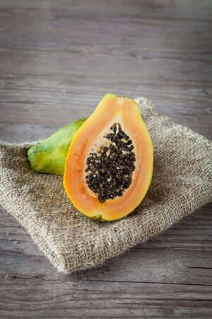 Sliced fresh papaya fruit on wooden background Standard-Bild